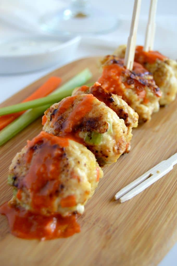 Buffalo Chicken Meatballs in a row on a serving board along side carrot and celery sticks