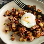 Individual serving of breakfast hash (potatoes, eggs, meat and onions)