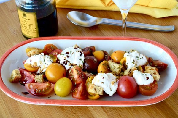 Take advantage of the season, make this Fresh Tomato and Burrata Salad recipe! The tomatoes are sweet and juicy, the fresh burrata mozzarella is creamy and delicious with the added salted crouton for that perfect crunch to hit on all of your food cravings!