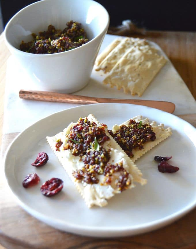 Cranberry Pistacio Spread on crackers next to a bowl of extra spread!