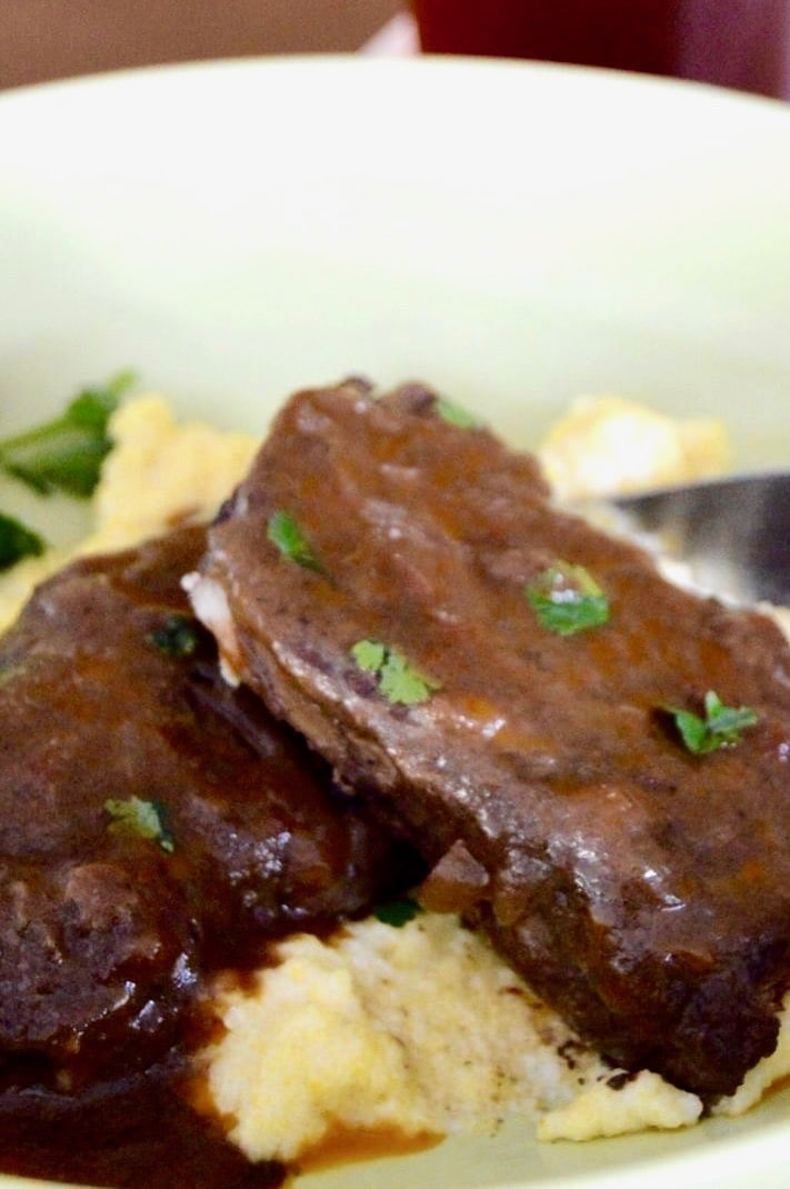 Braised Boneless Short Ribs with deep brown sauce over polenta in a serving bowl.