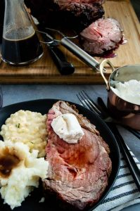 Prime rib on a plate in front of carving station of prime rib.