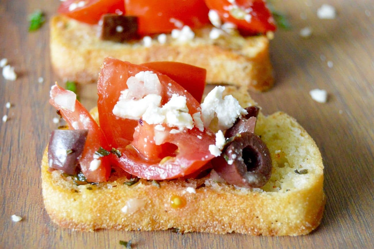 This recipe for Feta Kalamata Bruschetta (aka Greek Style) can be made no time at all and is packed with flavor. Creamy Feta, sweet, juicy tomatoes with just the right amount of salty kalamata olives! Put on top of your favorite toast or serve it alone as a simple salad!