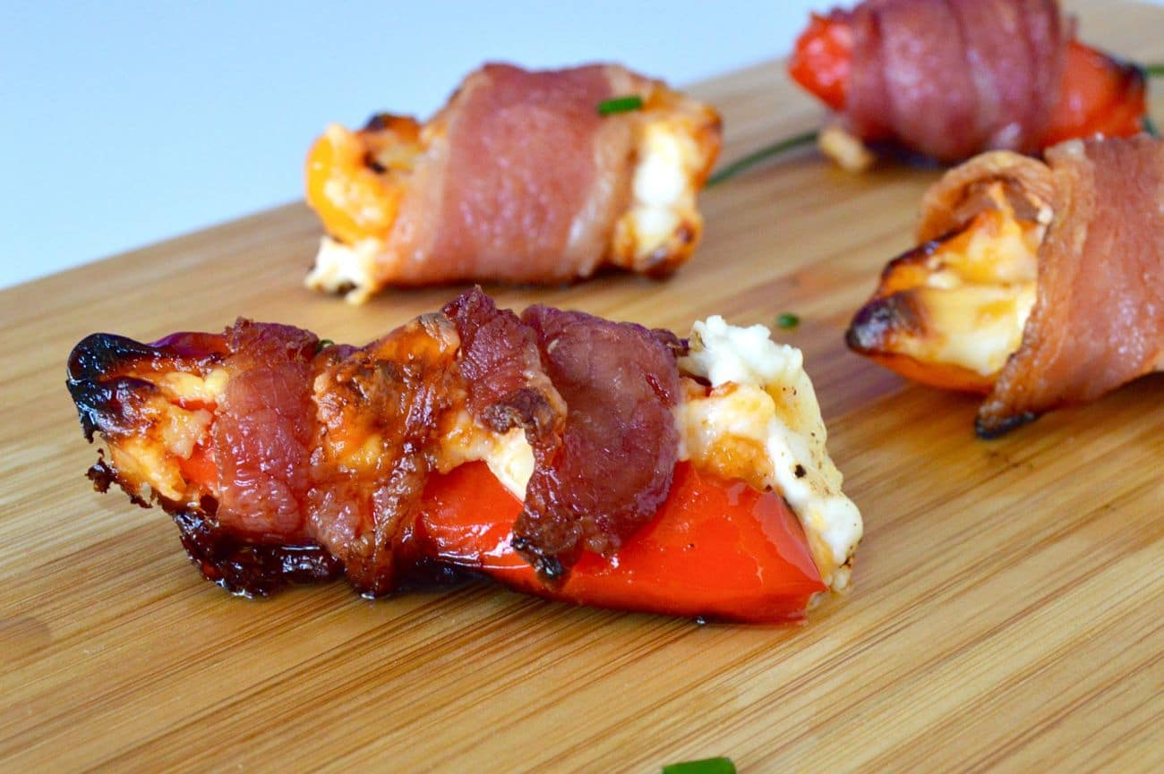 10 Amazing Game Day Appetizers Bacon Cheese Pepper Poppers a serving board with melty cheese dripping out