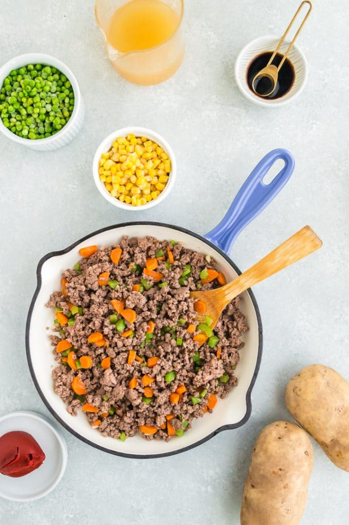 Sautéed ground beef with carrots and celery in a pan