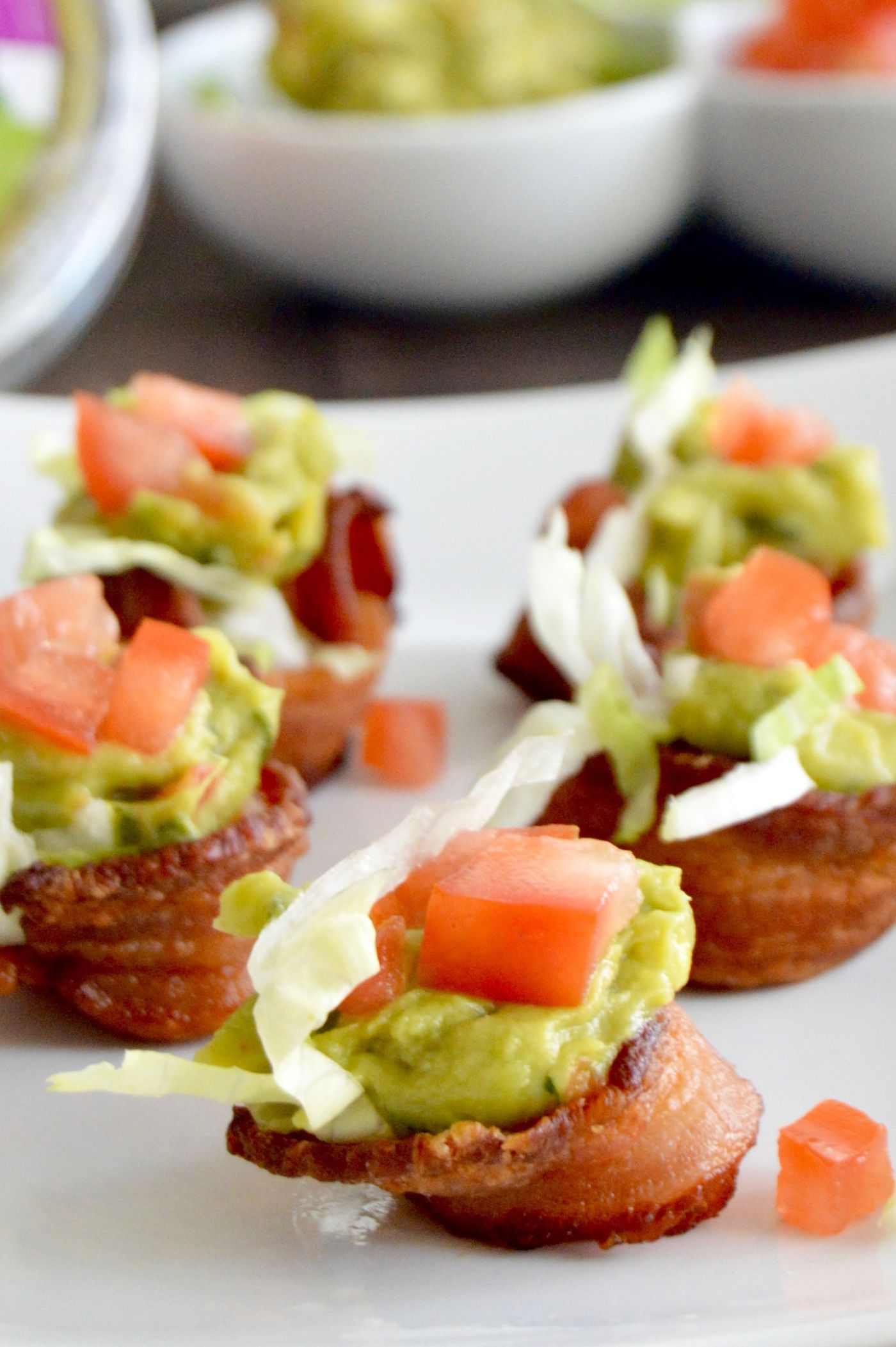Guacamole BLT Bacon Cups are a low carb appetizer or snack that can be made in about 15 minutes. Crisp lettuce, juicy tomatoes a dollop of Guacamole all in a bite sized crispy bacon cup!