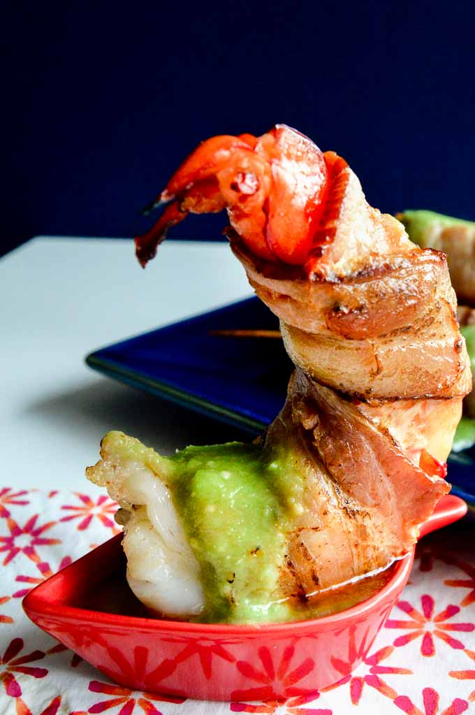 Single serving of a bacon wrapped around the shrimp with avocado sauce on top