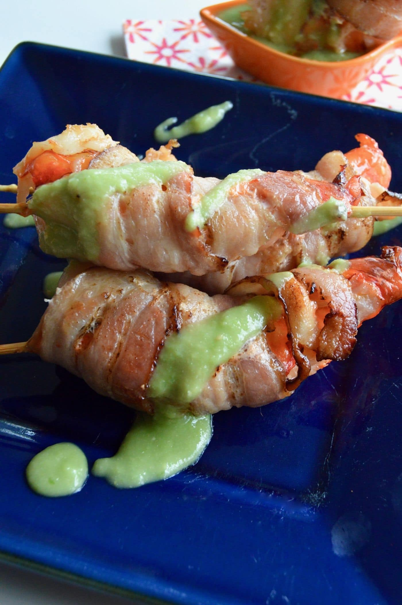 These Bacon Wrapped Shrimp with Avocado dip are 3 bite appetizers that will go quickly at any party! Succulent shrimp, wrapped in bacon broiled to perfection then served on skewers with a healthy avocado salsa!