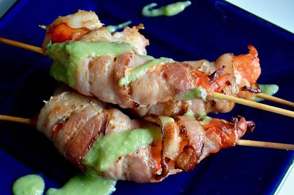 These Bacon Wrapped Shrimp with Avocado dip are 3 bite appetizers that will go quickly at any party! Succulent shrimp, wrapped in bacon broiled to perfection then served on skewers with a healthy avocado salsa! |appetizer|happy hour| Bacon|Superbowl party|
