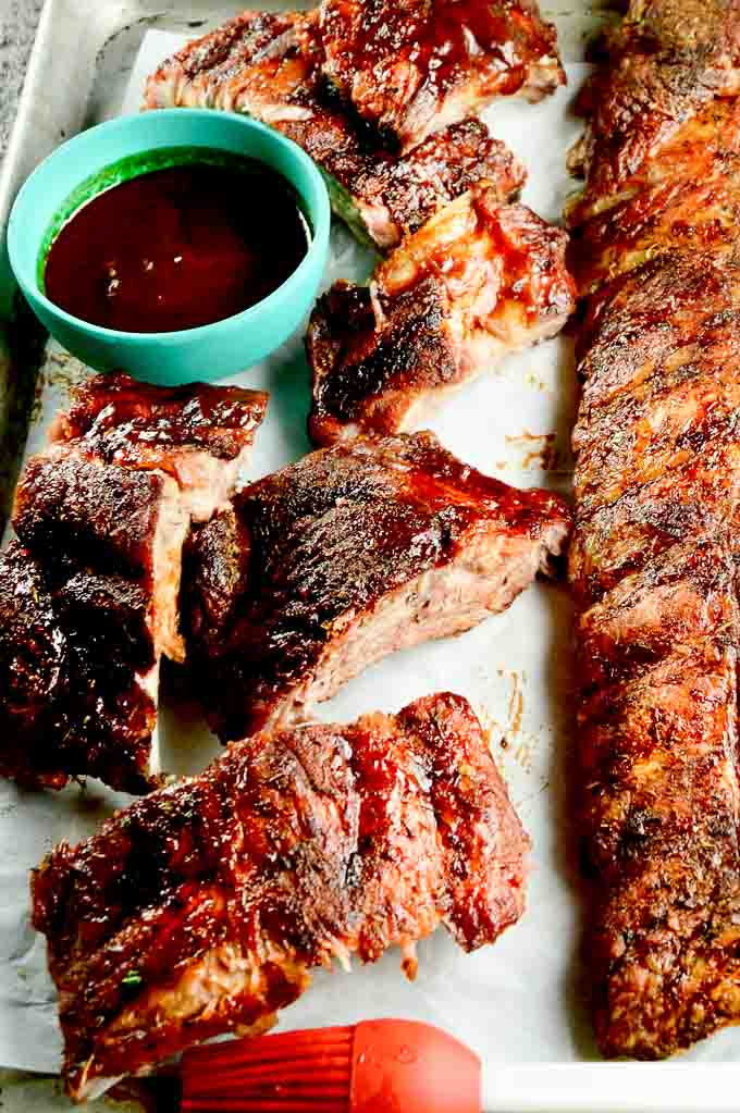 fall off the bone tender BBQ ribs, with a brush and a bowl of tangy bbq sauce on a serving tray. One whole rack, and one rack cut into bite sized pieces.