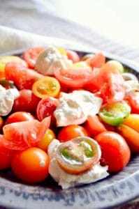 plate of tomato salad with fresh burrata on top