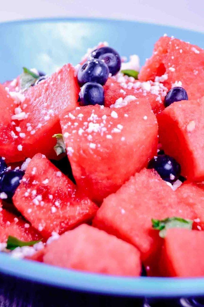 feta cheese atop watermelon chunks in a bowl