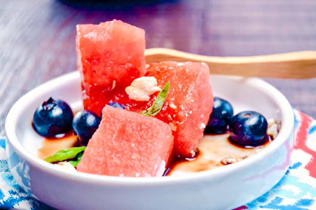 appetizer plate with watermelon and blueberries with a fork thru it