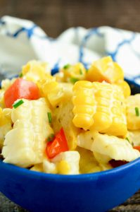 Fresh sweet corn, tomatoes in a blue bowl