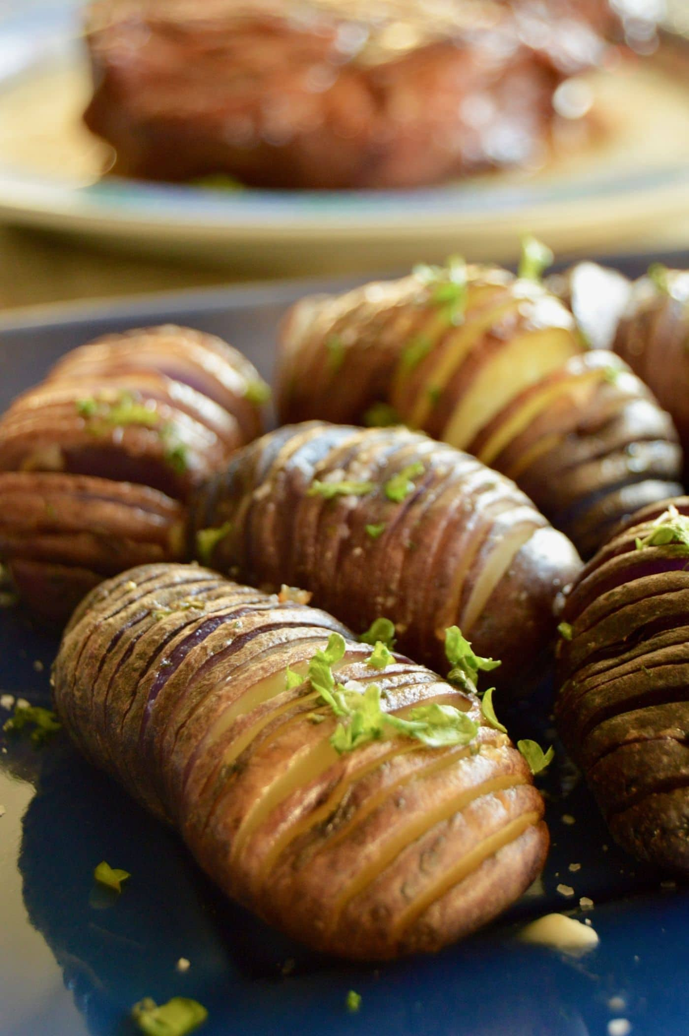 Grilled Sliced thin fan potatoes otherwise known as hasselback stuffed with herbs for a healthy side dish on a plate