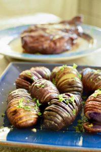 tray of crispy sliced hasselback potatoes on a buffet