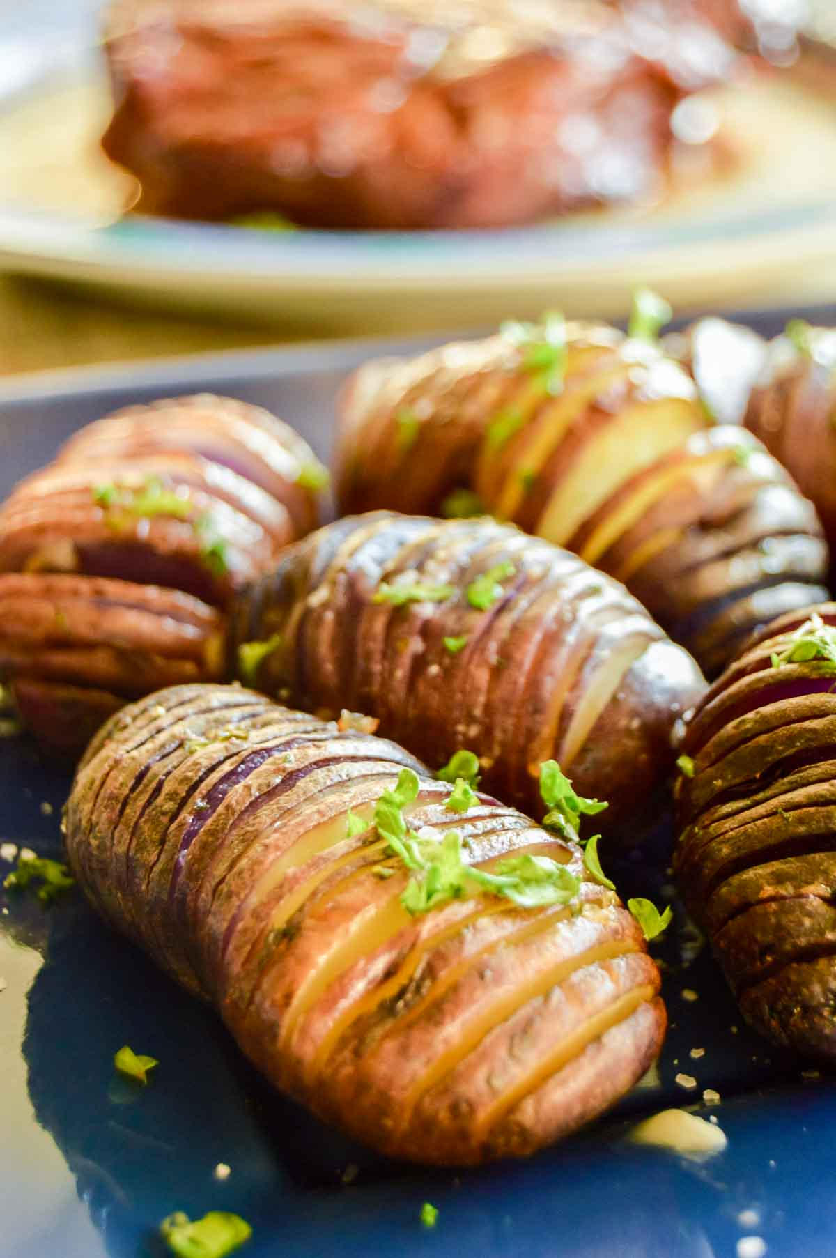 sliced hasselback potatoes with parsley on a blue plate