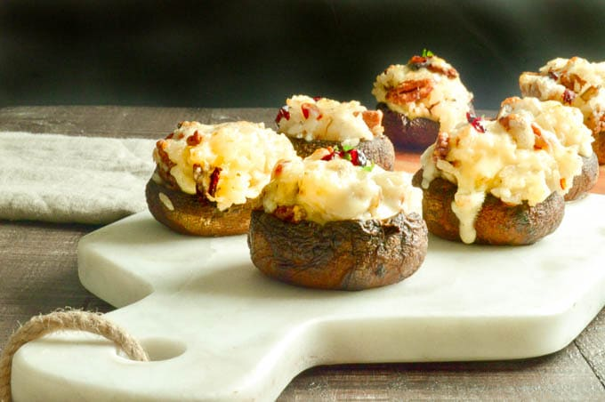 Serving platter of stuffed mushrooms caps with cheesy rice and cranberries