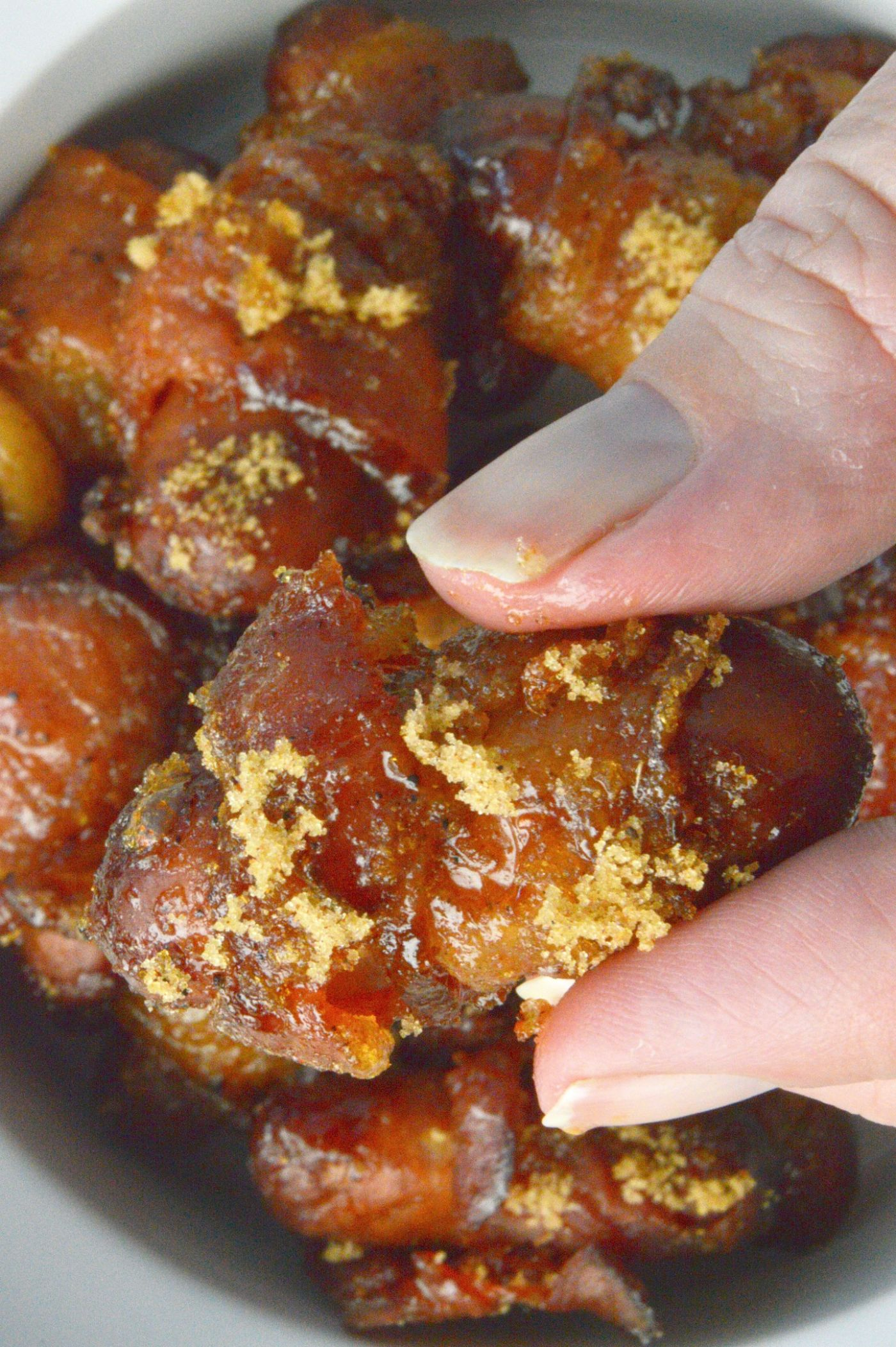 Holding a Spicy Sugar Bacon Smokies!! Crispy Bacon wrapped smokies are a bite sized treat that have a brown sugar coat that has a hint of spiciness! Perfect for game-day snacks or any casual cocktail party.