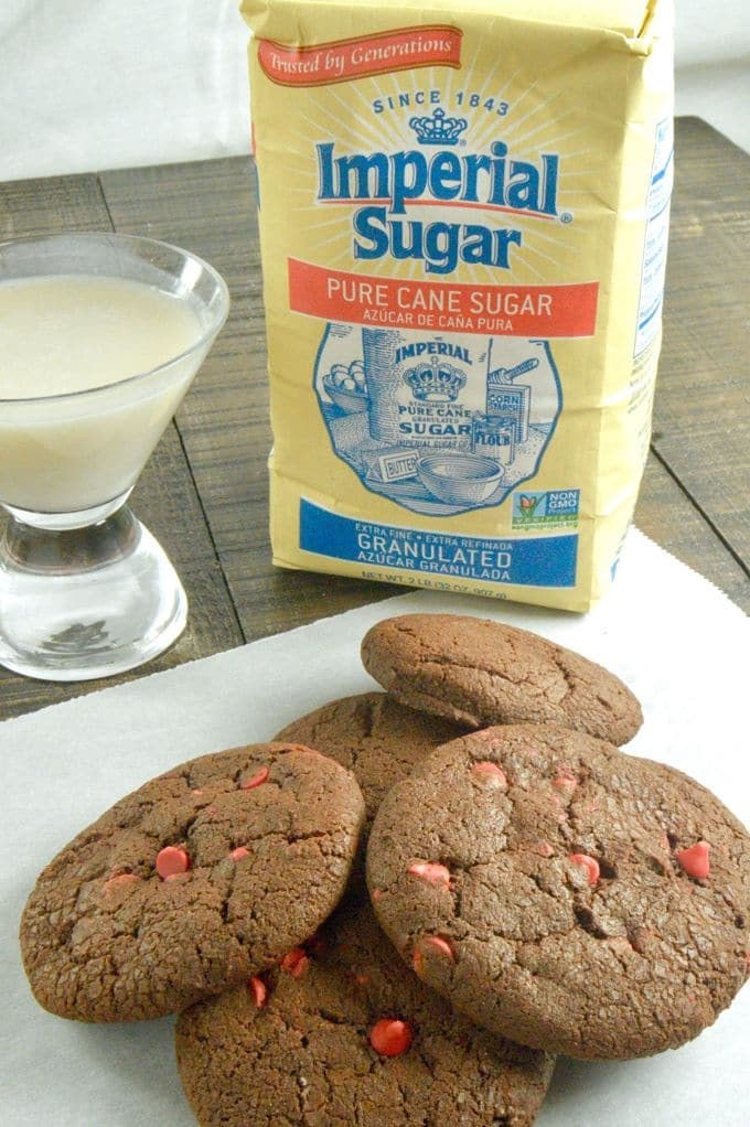 Chewy Chocolate cookies on a white parchment paper with a glass of milk and a pic of the Imperial Sugar Sponsor