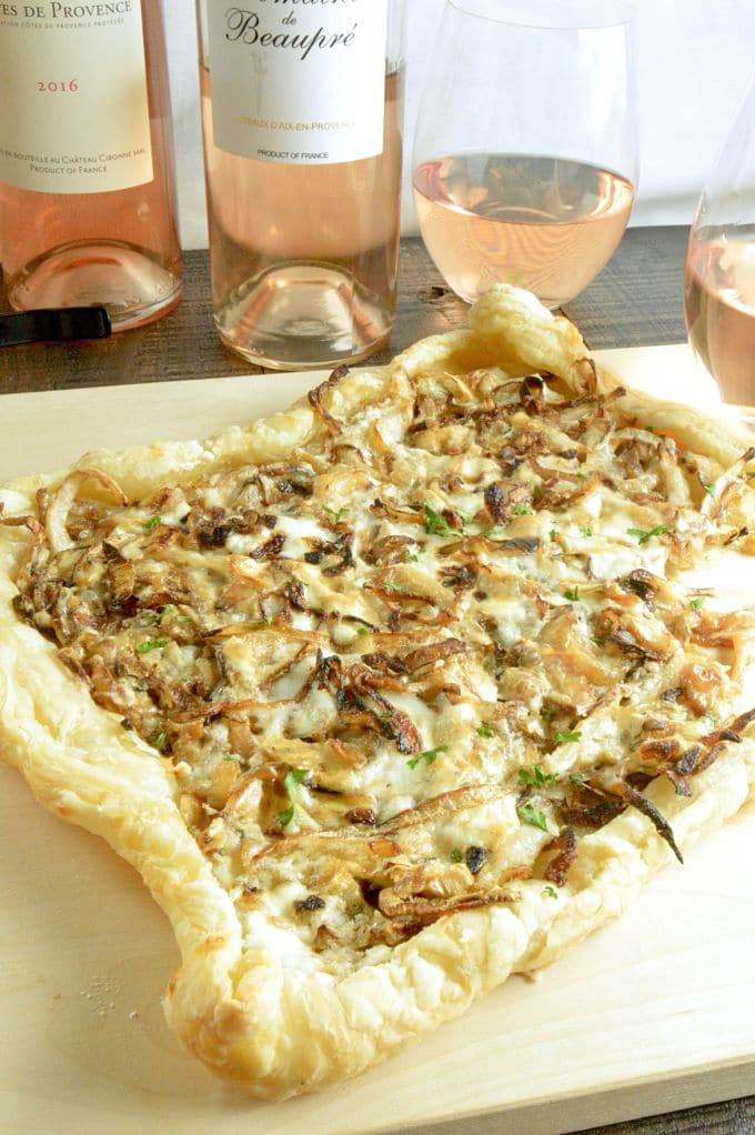 Caramelized Onion a top puff pastry for a French onion tart on a pizza board with wines of Provence in the background