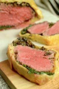 Beef Wellington Appetizers : shown with half finished puff pastry encased Wellington on a black plate with individual servings sliced off.