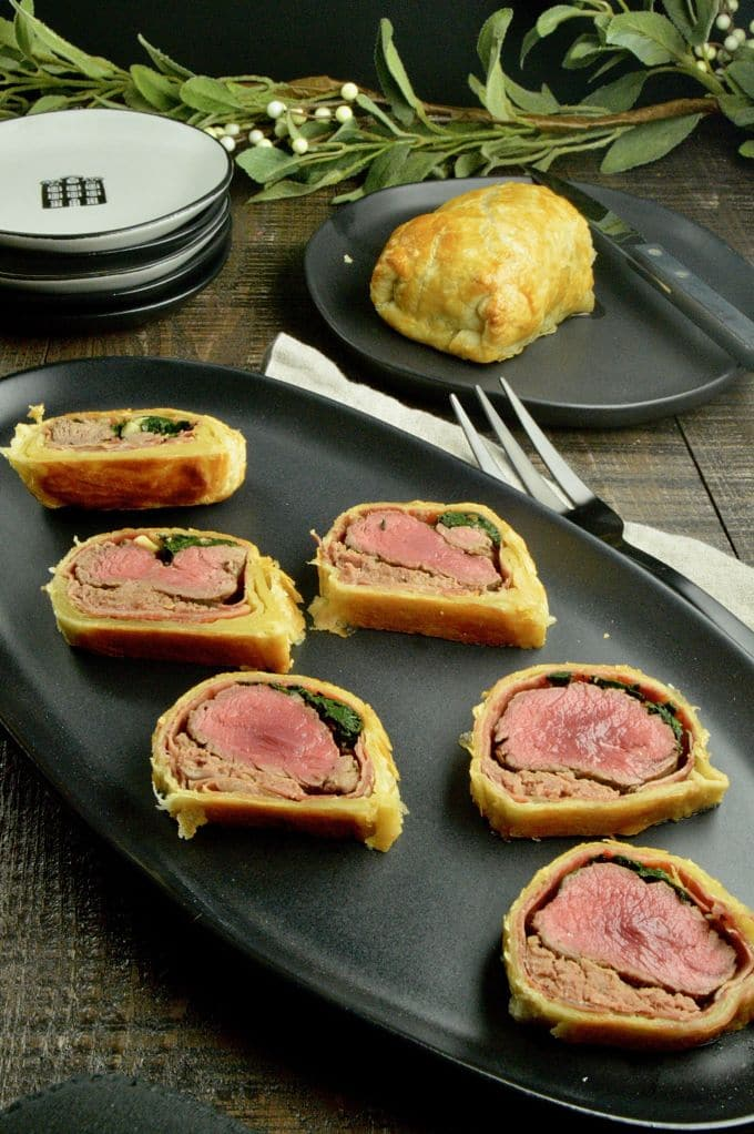 Beef Wellington Appetizers:  All cut on a black serving plate with the half of the log uncut in the background