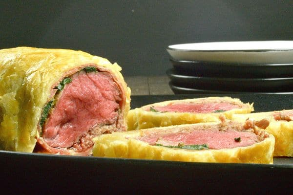Beef Wellington Puff pastry appetizers. Shown on a plate with them half of them cut and ready to eat.