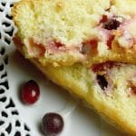 Close up Of Cut Cranberry Orange Bread with sugar drizzle on a cutout white plate