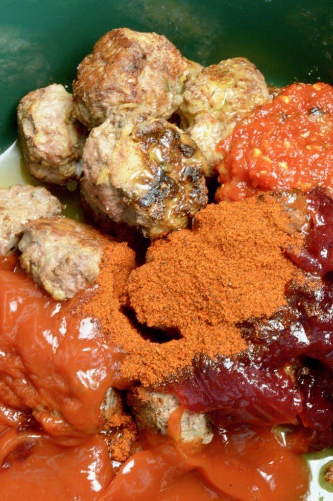 Cranberry Meatball ingredient shot. In a bowl, meatballs, chili powder, chili garlic sauce, orange juice, cranberry sauce .