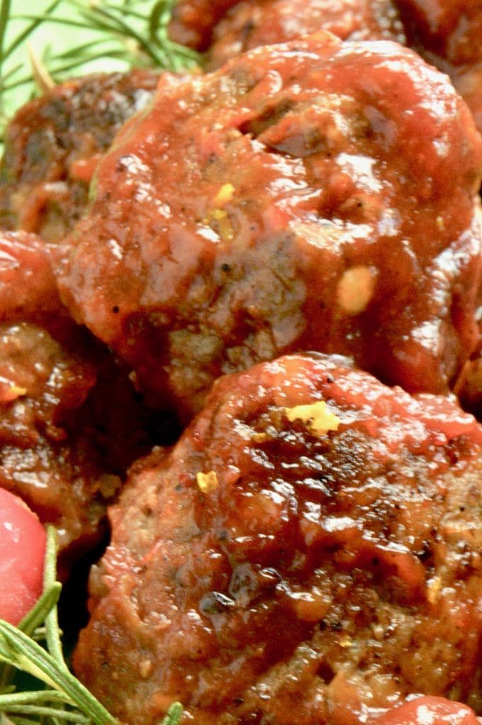 Vertical shot of Cranberry Orange meatball showing meatball covered in cranberry, orange sauce.