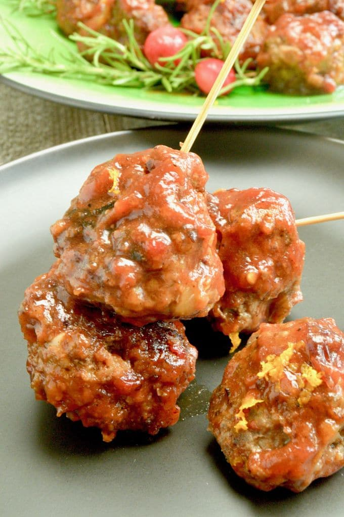 A black appetizer plate with 4 cranberry orange meatballs skewered with a toothpick with a platter of them on the plate behind them.