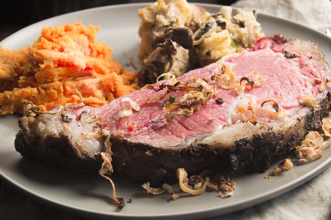 Dinner plate showing horseradish crust prime rib slice with sweet potatoes and Savory Bread pudding.