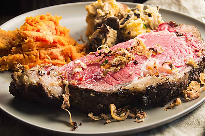 Horseradish Crust Ribeye Roast is tender, juicy and all the deliciousness you pay a fortune for at a fancy restaurant. Here a closeup of the mouthwatering slice on a dinner plate