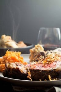 Dinner tabletop setting of Horseradish crusted Prime Rib Roast with a class of wine and a steaming bowl of fresh Mushroom Bread Pudding