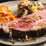 Horseradish Mustard Crusted Prime Rib Roast is tender, juicy and all the deliciousness you pay a fortune for at a fancy restaurant. Here a closeup of the mouthwatering slice on a tan plate with crunch horseradish tendrils galling off the meat.