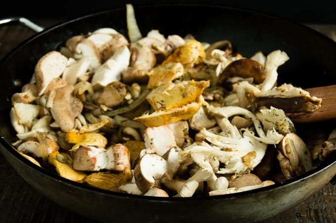 Chopped up mushrooms being sauteed in a pan with the onions for the Savory Bread Pudding
