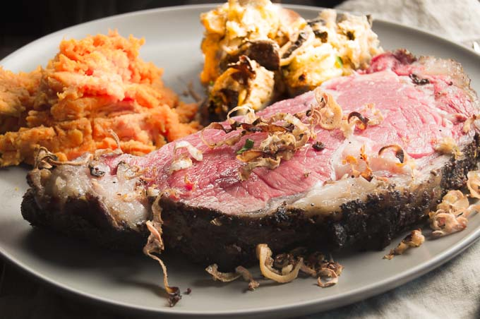 easy Savory Bread pudding on a dinner plate with a ribeye roast with crusted horseradish on top!