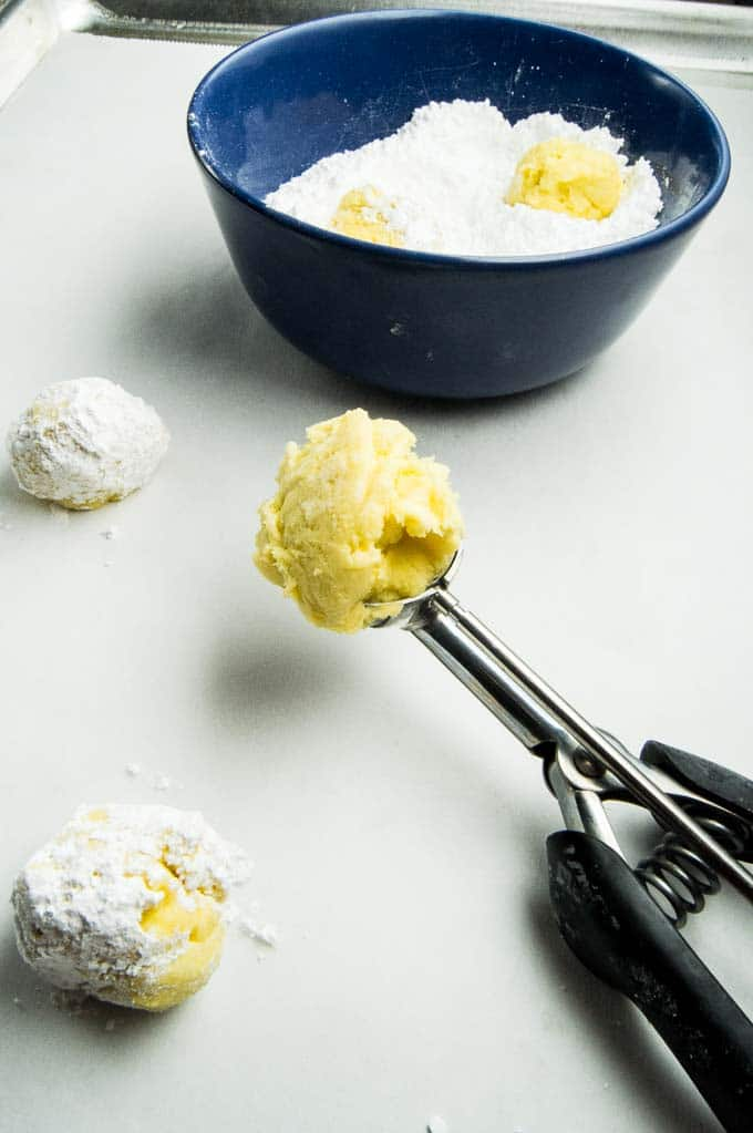Process shot of Gooey Lemon Butter cookies being made in a scoop and dipped into powdered sugar.