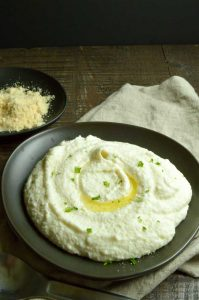 Creamy Cauliflower Puree in a black bowl drizzled with olive oil.