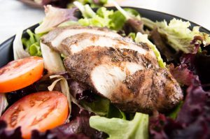 Grilled Jerk Chicken Salad with thick slices of jerk seasoned chicken breast.