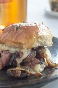 Close up of a melty cheese and onion laden roast beef slider