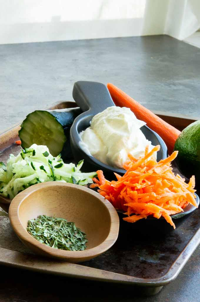 Ingredients on a tray to make tzatziki sauce : carrots, cucumber, spices, Greek Yogurt and lime juice
