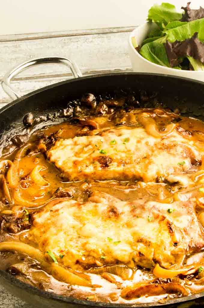 Smothered French French Onion Pork chops with melty cheese iin the one pan it was cooked in