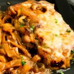 Melted Cheese atop French Onion Pork Chops on a plate