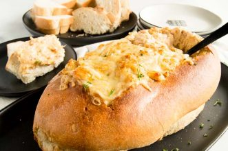 Hot Crab dip baked in a bread bowl on a plate.