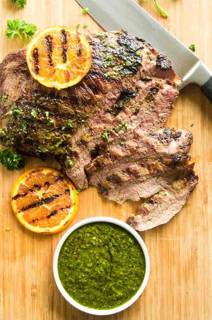 Flank Steak with chimichurri sauce sliced on a cutting board.
