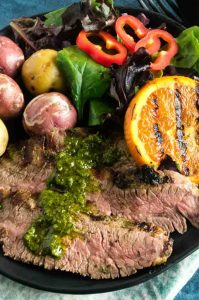 Chimichurri Sauce from Argentina over the sliced flank steak with a salad