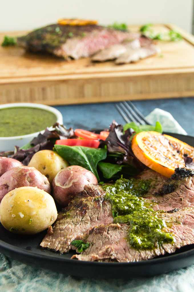 Sliced flank steak topped with a spoonful of fresh chimichurri sauce.