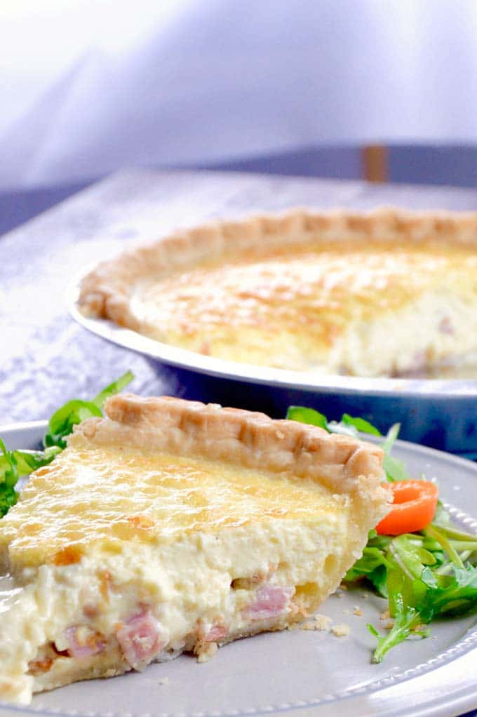 slice of quiche on a gray plate with a salad